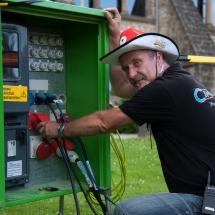 Unser IT'ler Thomas verlegt vor jedem Spiel etliche Meter Kabel quer über die Wiese. Er hat den Überblick über die gesamte Technik, Beleuchtung und Anschlüsse für die Getränke- und Lebensmittelwagen.